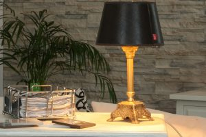 An old-style lamp on the desk in front of wall with stone decoration.