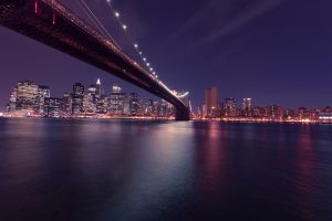 A view of the Brooklyn Bridge and NY by night.