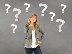 A woman with a lot of question marks around her head because she cannot decide whether buying or building a home is the right choice for her.