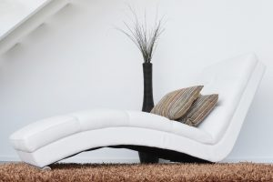 A modern white sofa and brown carpet.