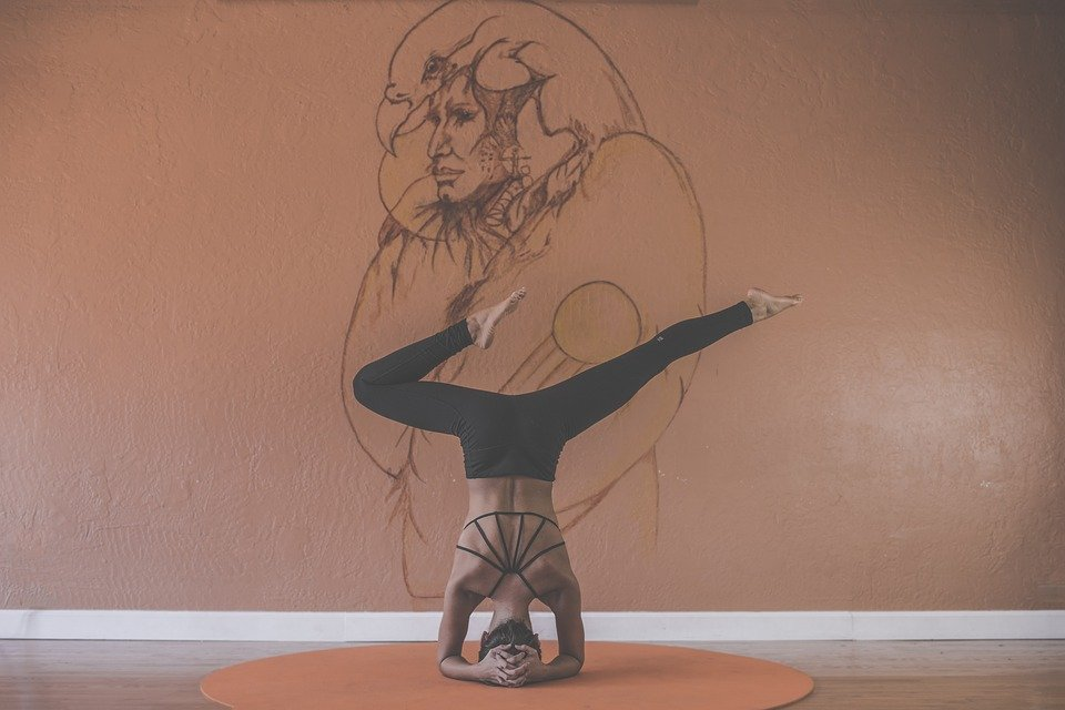 a girl doing yoga poses in front of a drawing on a wall