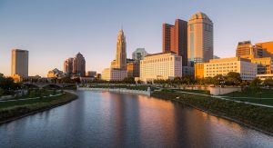 Buying a house in Columbus remotely will save you a lot of time. Here is all you need to know. Alt text: view of the river in downtown Columbus, Ohio.
