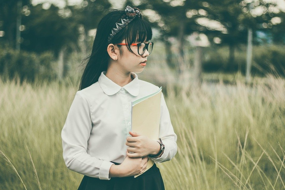 a little girl with glasses, holding her notebook.