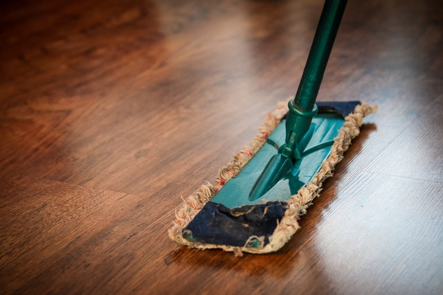 A person cleaning their wooden floor with a mop in order to get rid of their NYC house pest problem.