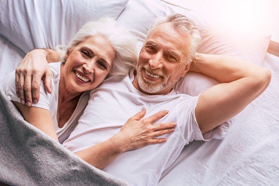 an elderly couple in bed, relaxing and enjoying life.