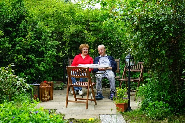 An older couple sitting at the garden table and relaxing.