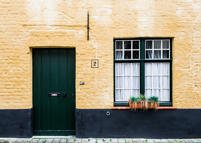 A yellow wall with a green door and window.