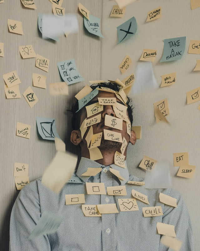 A stressed-out man covered with to-do post-its who's trying to find a way to reduce stress when buying a house.
