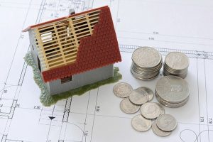 A small model house and some coins.