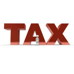 A figurine standing in front of the word tax, as not paying taxes is one of the most important benefits of first-time homebuyers.
